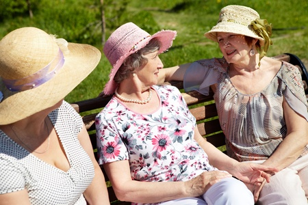 Portrait of senior women sitting on the bench in open air    photo