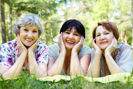 Portrait of senior women resting on grass and looking at camera  photo