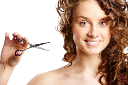 Curly woman with scissors smiling at camera photo