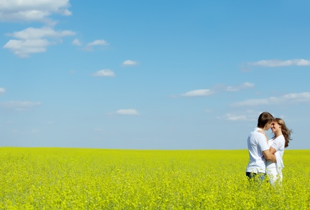 lifestyle: Image of happy couple embracing in yellow meadow at summer