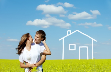 Image of happy couple in yellow meadow with drawn house on background photo