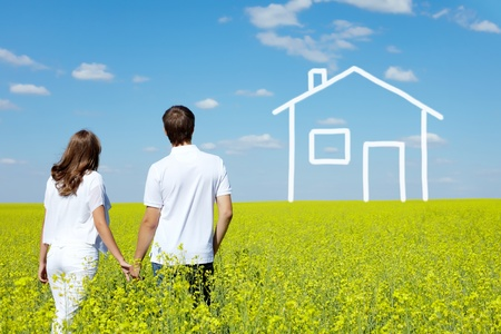 Back view of amorous couple in yellow meadow looking at drawn house Фото со стока