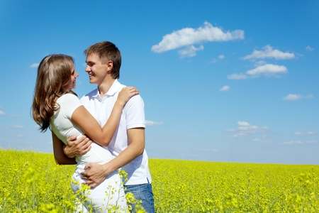 Image of happy couple embracing in yellow meadow at summer photo