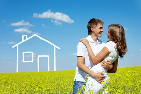 Image of happy couple embracing in meadow with drawn house on background photo