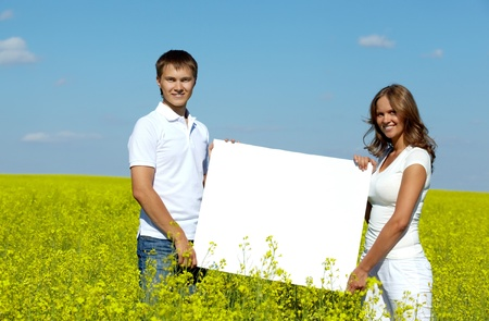 Portrait of happy young couple with blank paper standing in meadow  photo