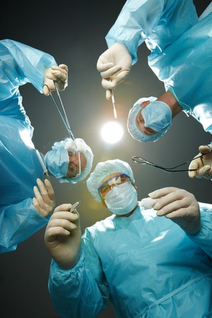 bending over: Three surgeons bending over a patient with forceps