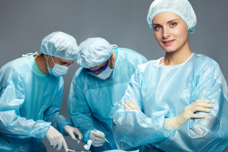 female surgeon: A young female surgeon against her two male colleagues
