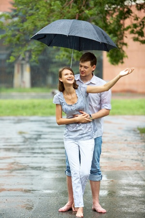 Portrait of woman and man walking under umbrella during rain     photo