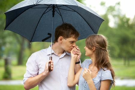Portrait of young man kissing girl's hand under umbrella outdoors     photo