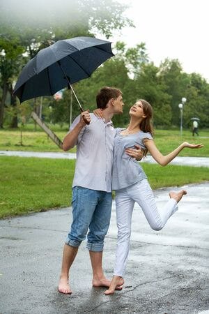 Portrait of woman and man under umbrella during rain     photo