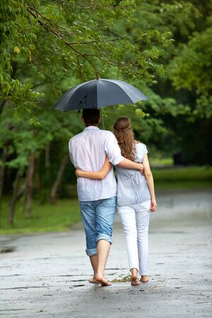Back view of woman and man walking under umbrella during rain     photo