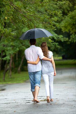 couple WALKING: Back view of woman and man walking under umbrella during rain