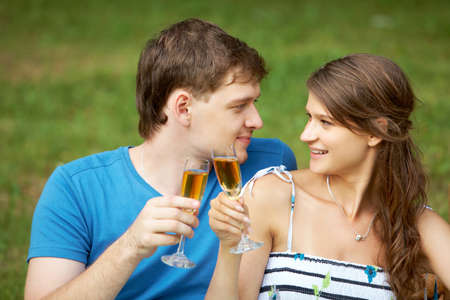 Portrait of man and his girlfriend holding flutes with alcohol and looking at each other photo