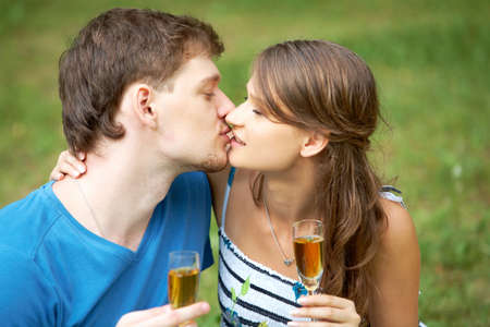 Portrait of man and his girlfriend holding flutes with alcohol and kissing photo