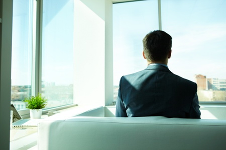ceo: Back view of businessman sitting on sofa in office