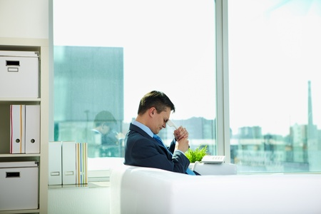 tired businessman: Sad businessman sitting on sofa with phone receiver in office