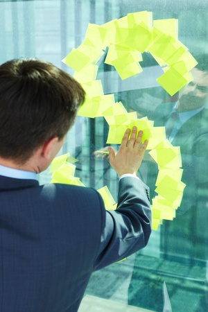 Back view of businessman sticking blank notepaper on window photo