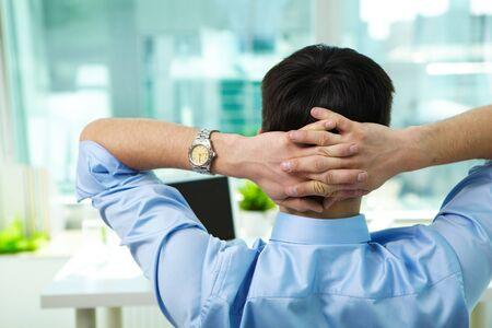 rear: Back view of businessman having break in office Stock Photo