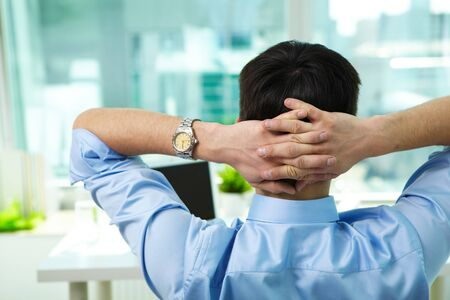 Back view of businessman having break in office Stock Photo