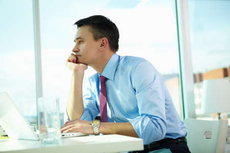 Portrait of pensive man with laptop in office photo