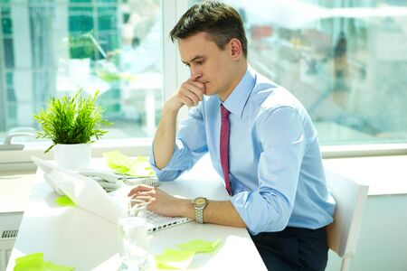 Portrait of pensive man typing in office Stock Photo - 9571760