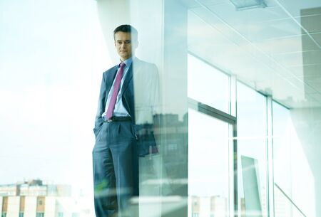 serious guy: Portrait of confident man standing by the window in office