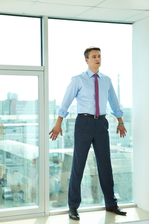 Portrait of confident man standing by the window in office photo