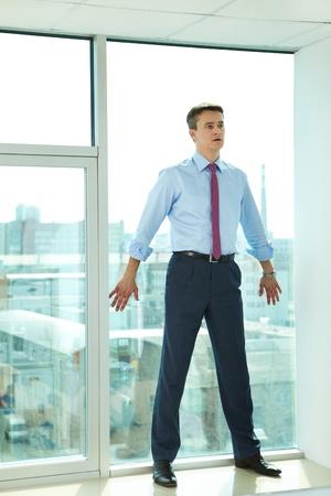 hombre asustado: Retrato de hombre de confianza permanente por la ventana en la Oficina Foto de archivo