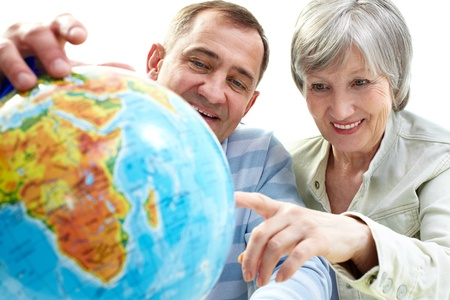Portrait of happy senior couple looking at globe photo