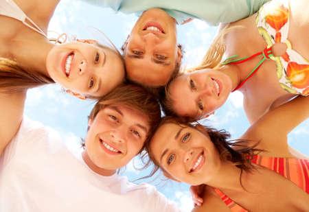 teen bikini: Below view of joyful teens embracing and looking at camera with smiles