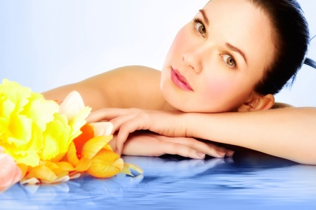 Gorgeous woman lying on blue water surface and looking at camera photo