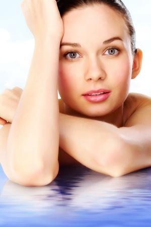 elleboog: Prachtige vrouw camera kijken terwijl liggend op blauwe wateroppervlak Stockfoto