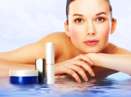 face cream: Beautiful woman with professional makeup lying on water surface with cosmetic products near by Stock Photo