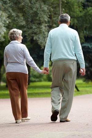 senioren wandelen: Achteraanzicht van senior paar wandelt in het park en chatten Stockfoto