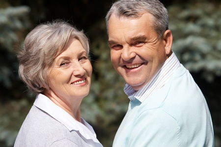 Portrait of happy senior couple looking at camera on sunny day photo