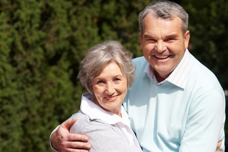Portrait of happy senior couple embracing each other and looking at camera Stock Photo - 9571728