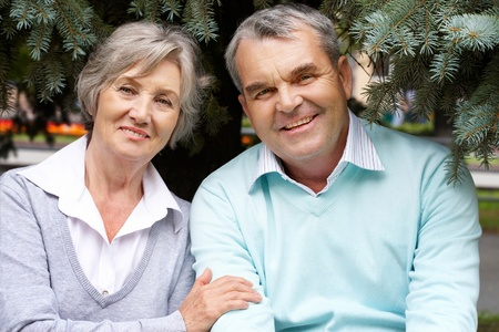 Portrait of happy senior couple looking at camera outdoors photo