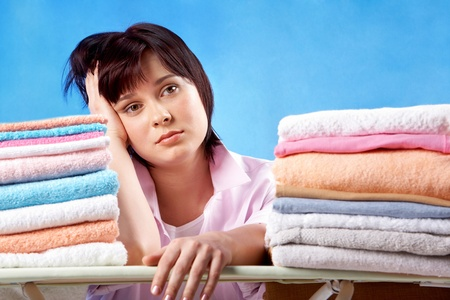 An upset woman sitting at heaps of ironed towels  photo