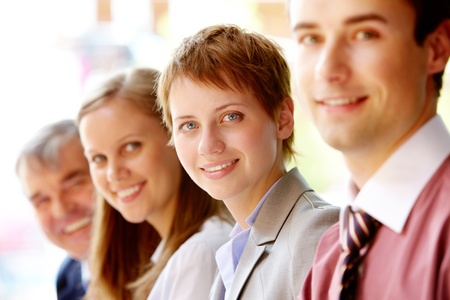 Group of happy successful people in line with focus on woman  photo