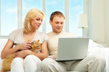 A young couple sitting on sofa and looking at laptop screen  photo