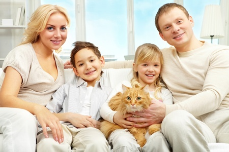 A young family with two children sitting on sofa, looking at camera and smiling Stock Photo - 9571826