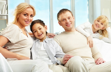 A young family of four sitting on sofa, looking at camera and smiling Stock Photo - 9571809
