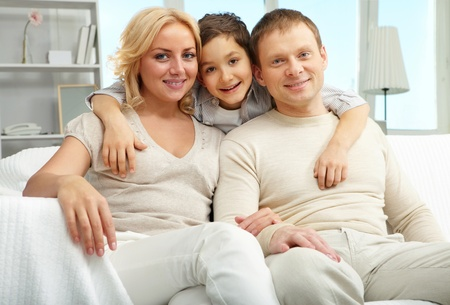 A family with son embracing, looking at camera and smiling Stock Photo - 9571828