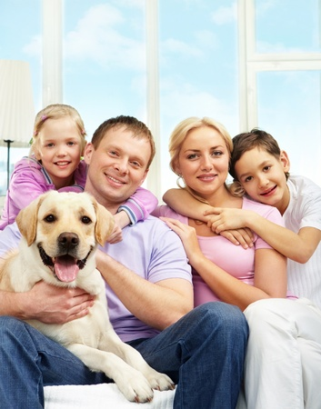 animal family: A young family of four with a dog sitting on sofa, looking at camera and smiling Stock Photo