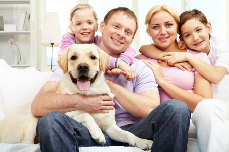 animal family: A happy family of four with a dog sitting on sofa, looking at camera and smiling