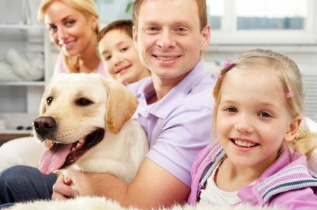 mujer perro: Una familia feliz de cuatro con un perro sentado en el sof�, el objetivo es la hija