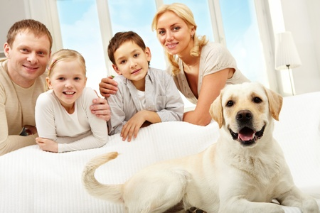 pet: A big dog lying on sofa, a family of four standing behind  Stock Photo