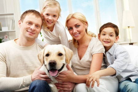 Portrait of a happy family sitting on sofa with a dog, looking at camera and smiling photo