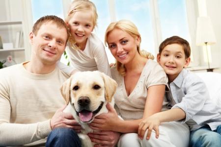 Retrato de una familia feliz, sentado en el sofá con un perro, mirando a la cámara y sonriente