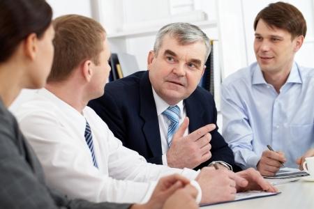 talking businessman: Un hombre de negocios senior hablando con sus colegas
